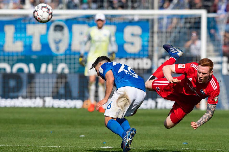 David Bates klärt mit einer artistischen Flugeinlage den Ball vor Bochums Görkem Saglam.
