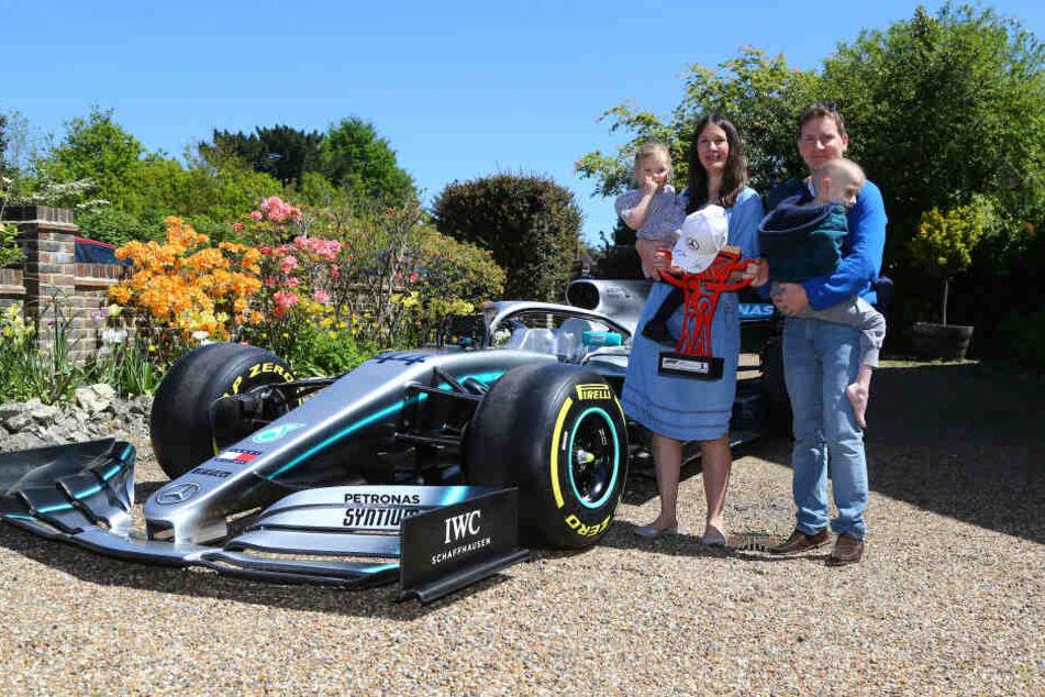 Harrys Schwester Georgia, Mutter Charlotte, Vater James neben einer Nachbildung des Rennwagens von Lewis Hamilton. Harry Shaw hatte seinem Idol Hamilton in einer Nachricht viel Glück für das Rennen in Spanien geschickt. Hamilton antwortete ihm.