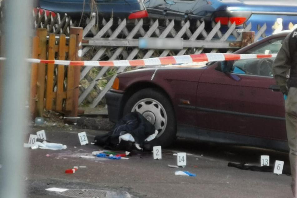 Markierungen der Polizei liegen nach der Messerstecherei neben einem Auto auf der Strasse.
