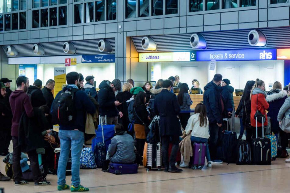 Fluggäste warten in der Abflughalle des Flughafens vor einem Ticketschalter. (Archivbild)