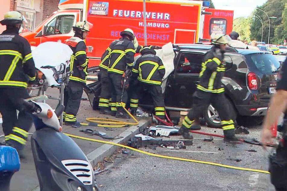 Feuerwehrleute versuchen, eingeklemmte Menschen aus dem Auto zu befreien.
