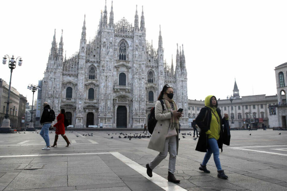 Fast menschenleer ist der Platz vor dem Mailänder Dom. Eine Frau traut sich nur noch mit Mundschutz raus.