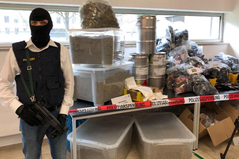 Ein bewaffneter Polizeibeamter steht im bayerischen Kriminalamt neben der Präsentation einer Drogenproduktionsstrecke und einiger Luxusprodukte aus der Wohnung eines Drogenproduzenten in München.