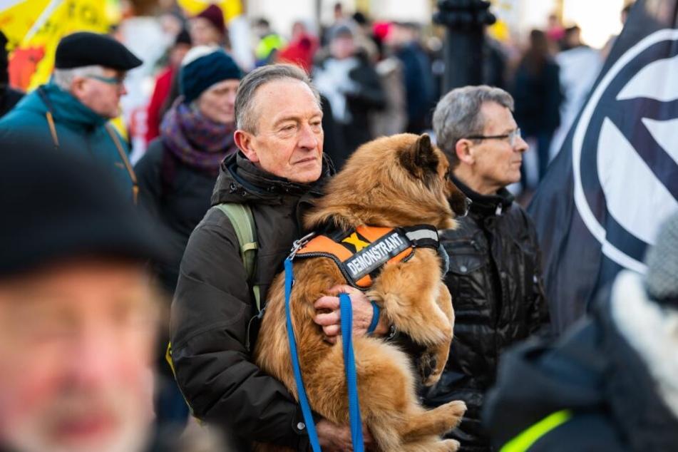"""Bei der Demonstration gegen die Brennelementefabrik Lingen trägt einer der Atomkraftgegner seinen Hund, der ein Hundegeschirr mit der Aufschrift """"Demonstrant"""" trägt, auf dem Arm."""