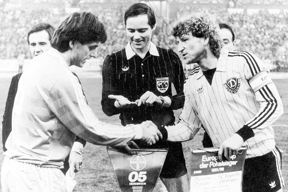 """Ein geschichtsträchtiges Foto vom 5. März 1986: """"Dixie"""" Dörner (r.) und Uerdingens Kapitän Matthias Herget beim Wimpeltausch vor dem Anstoß des Viertelfinals im UEFA-Pokal zwischen Dynamo und Bayer. Dresden gewann das Hinspiel 2:0, verlor zwei Wochen spät"""