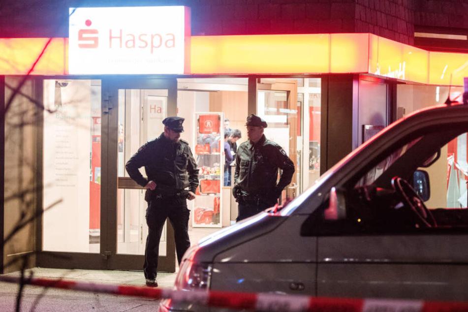 Polizisten stehen im Eingangsbereich der überfallenen Sparkasse.