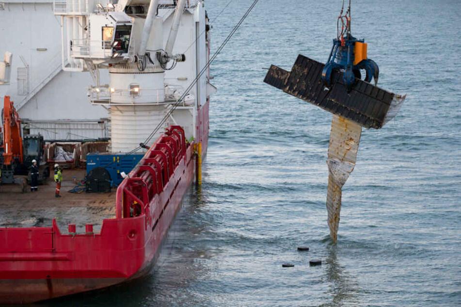 Der Bergungsschiff hebt einen zerstörten Container vom Nordseegrund.