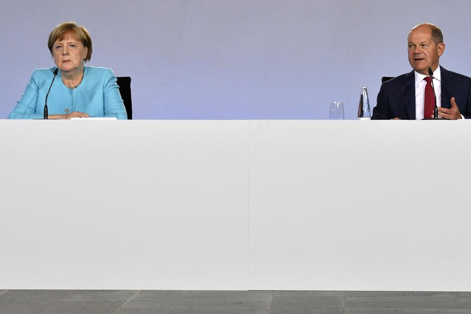 Bundeskanzlerin Angela Merkel (65, CDU) und Bundesfinanzminister Olaf Scholz (62, SPD) sitzen bei einer Pressekonferenz im Bundeskanzleramt.