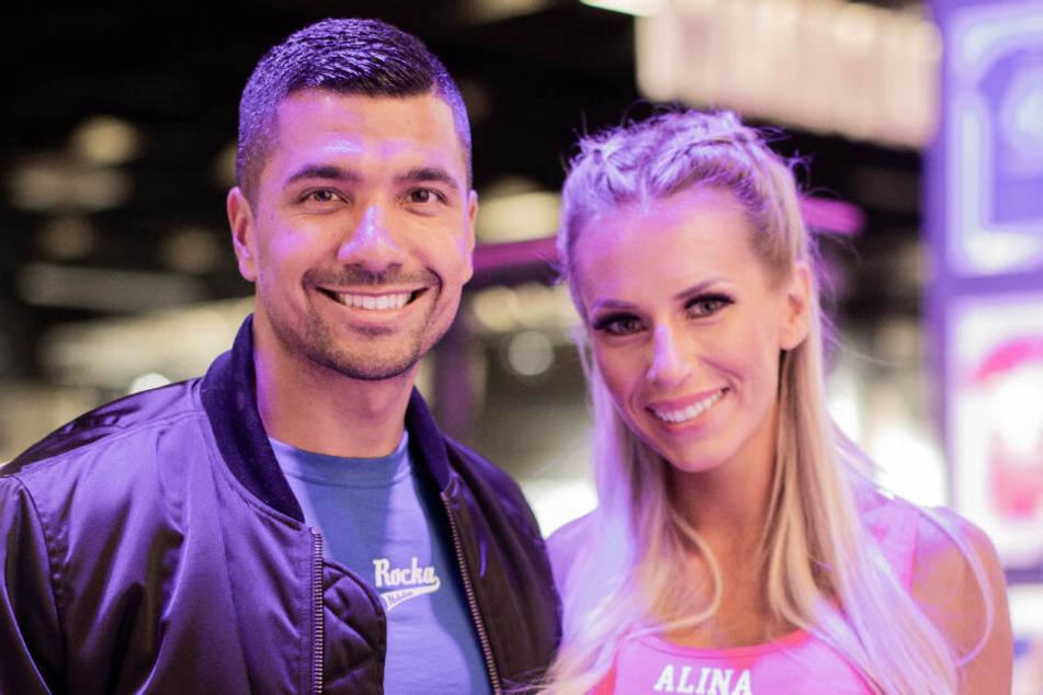Julian Zietlow, Gründer und Chef von Rocka und BumBum, und seine Frau Alina Schulte im Hoff, Influencerin, stehen auf ihrem Messestand auf der Fitnessmesse Fibo.