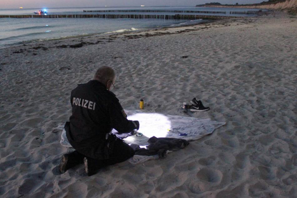 Ein Beamter untersucht die zurückgelassenen Kleidungsstücke.