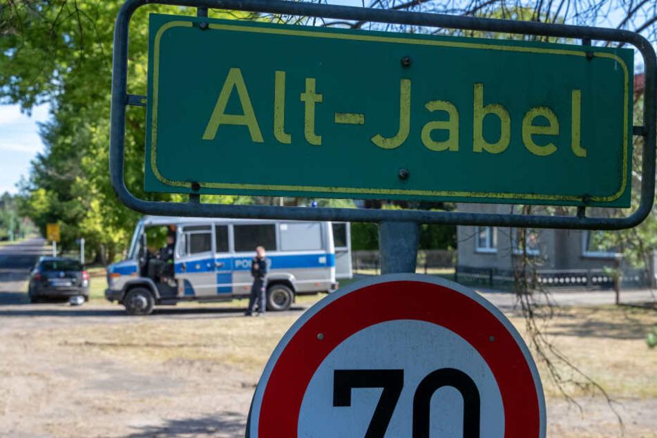 Polizisten sperren die Zufahrt zum noch immer evakuierten Ort Alt Jabel.