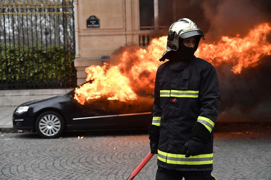 Ein Feuerwehrmann steht während der Proteste und Unruhen in Paris vor einem brennenden Auto im 8. Bezirk.