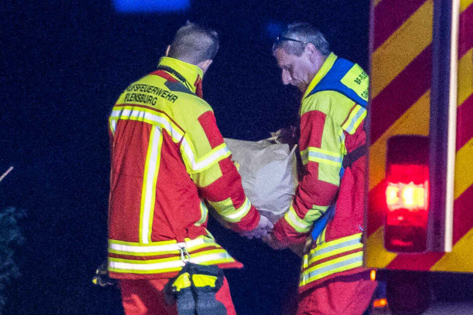 Zwei Feuerwehrleute tragen den Stein von der A7.