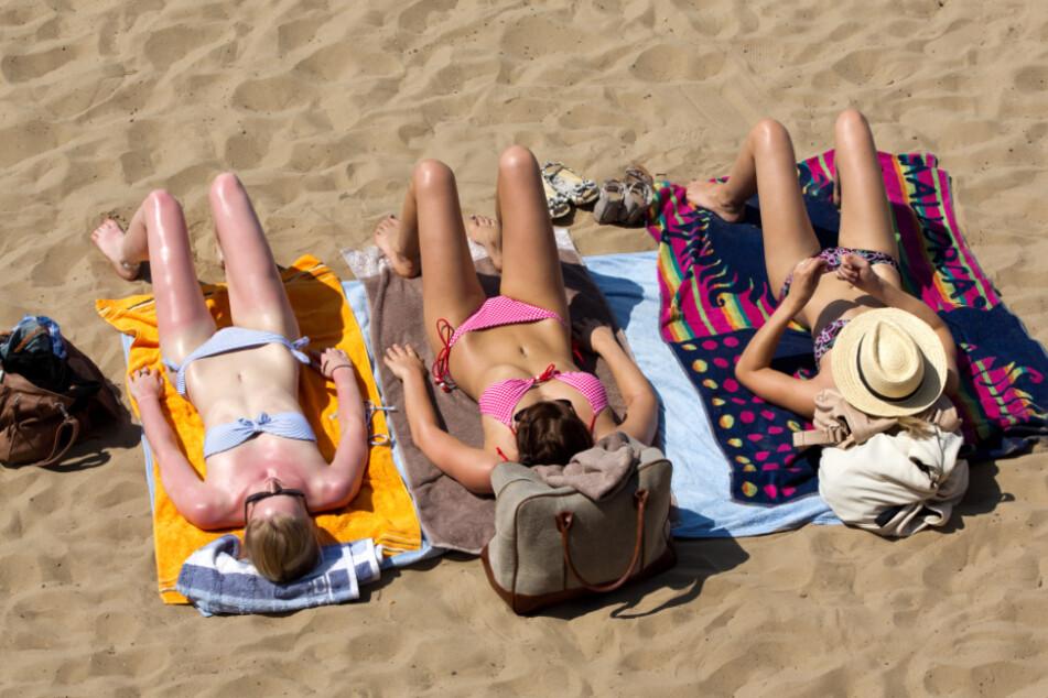 Drei junge Frauen genießen ihren Sommerurlaub am Strand. (Symbolbild)
