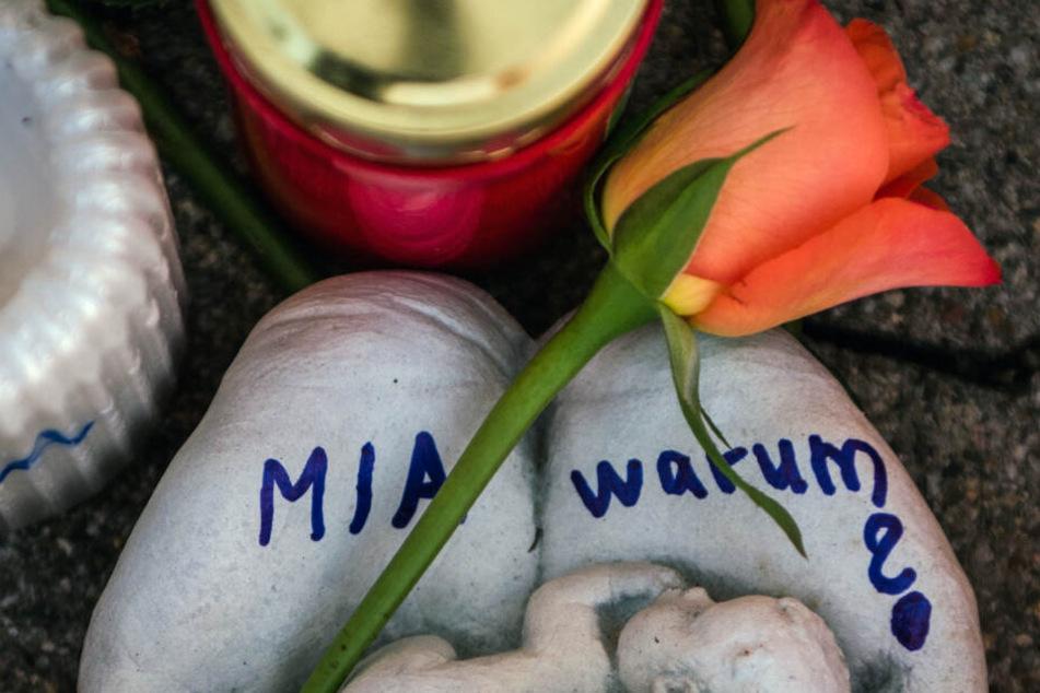 """Eine Skulptur in Form zweier Handflächen mit der Aufschrift """"Miawarum?"""" und eine Rose liegen vor dem Tatort (Archivbild)."""