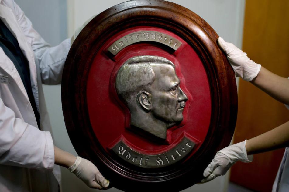 Mitarbeiter der Bundespolizei zeigen in Argentinien ein Relief von Adolf Hitler.