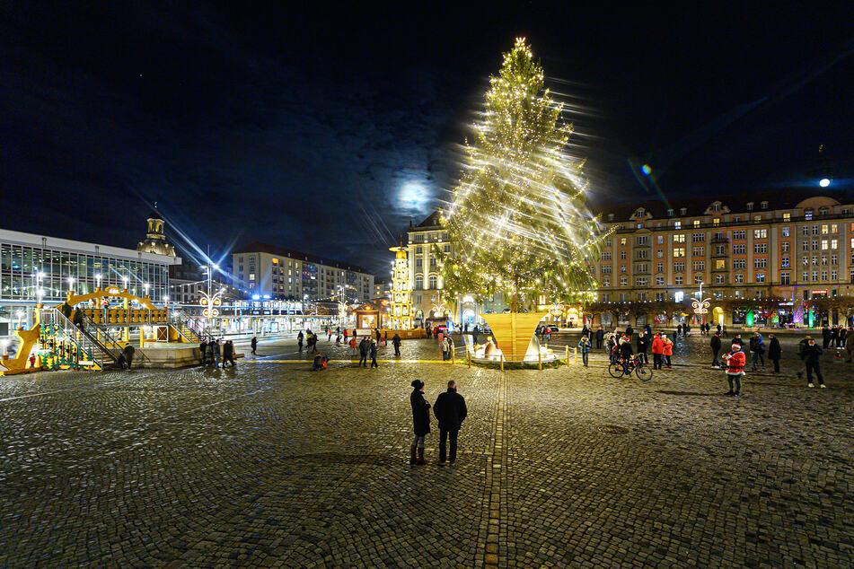 Nur wenige Menschen versammeln sich um einen überdimensionalen Schwibbogen, eine Pyramide und einen Weihnachtsbaum auf dem Dresdner Altmarkt. Der Striezelmarkt fällt dieses Jahr aus.