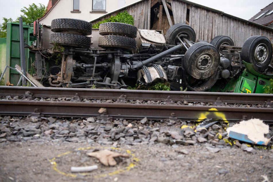Teile liegen nach der Kollision eines Lastwagens mit einem Zug auf den Gleisen vor dem umgekippten Fahrzeug.