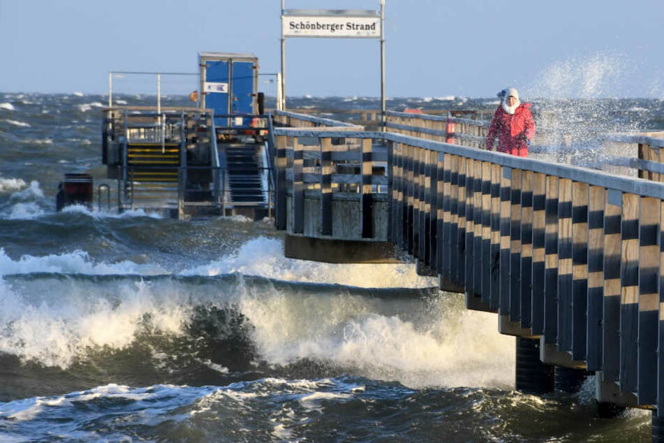 Hohe Wellen treffen an der Seebrücke auf den Schönberger Strand bei Kiel.