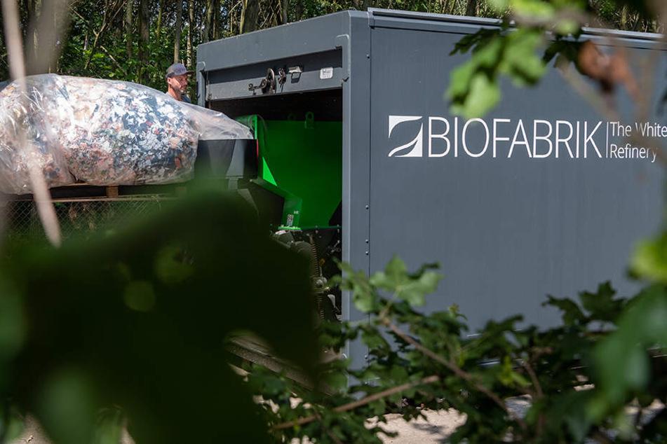 """Ein Mitarbeiter der Biofabrik White Refinery GmbH schüttet in die """"WastX Plastic"""" Anlage Plastikmüll zur Rückverwandlung von Öl."""