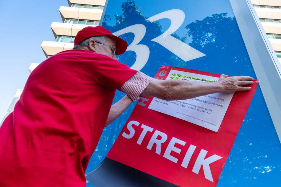 """Ein Plakat mit der Aufschrift """"Streik"""" wird vor dem Funkhaus des bayerischen Rundfunk aufgehängt"""
