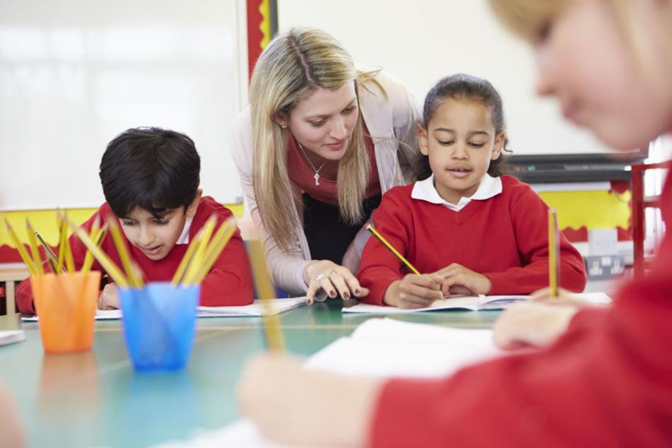 Kinder beim Unterricht mit ihrer Lehrerin (Symbolbild).