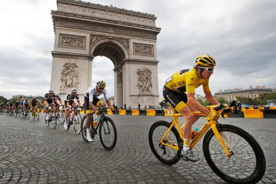Eine Gruppe Radsportler fährt während der Tour de France am Arc de Triomphe in Paris vorbei.