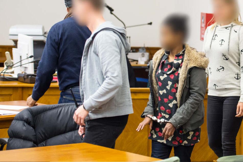 Zwei Justizmitarbeiter führen die Angeklagter während des ersten Prozesses in den Gerichtssaal.