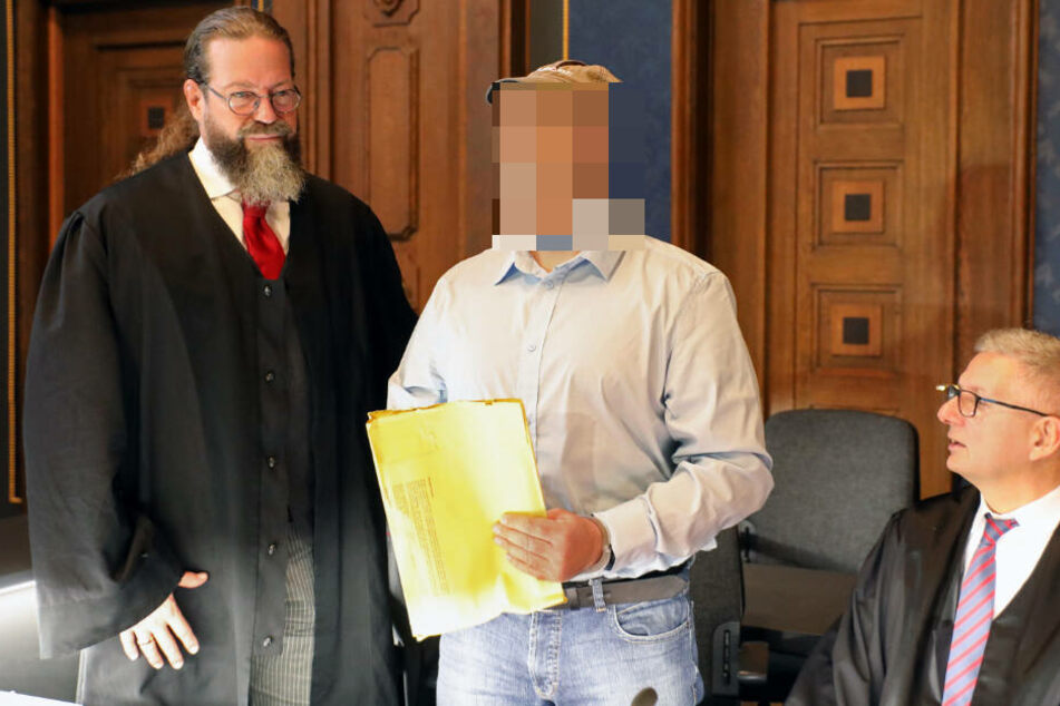 Der Angeklagte (Mitte) steht zwischen seinen beiden Verteidigern.