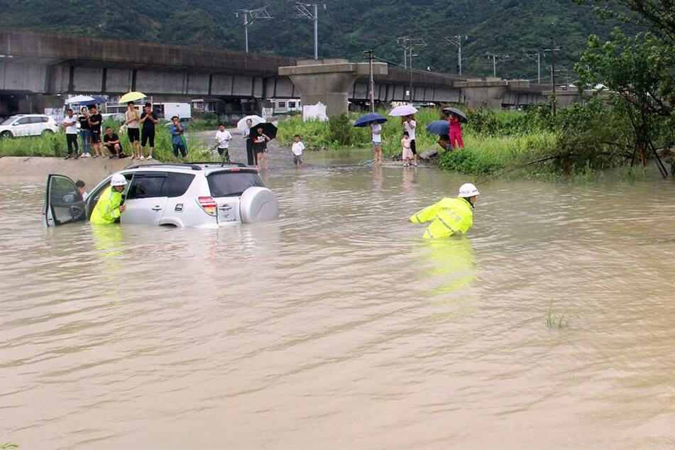 Verkehrspolizisten versuchen ein Auto aus den Fluten zu ziehen.