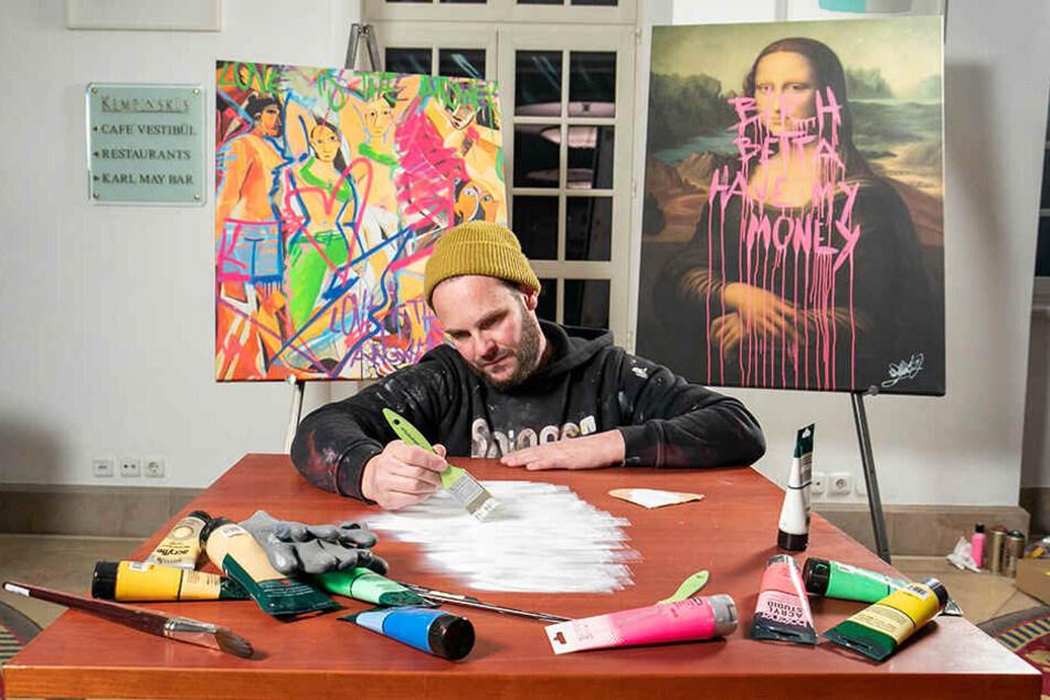 """René Turrek legt in der Mitte der Tischplatte das """"Gesicht"""" mit Acrylfarben an."""