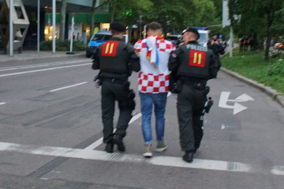 Polizeibeamte führen einen kroatischen Fan ab.