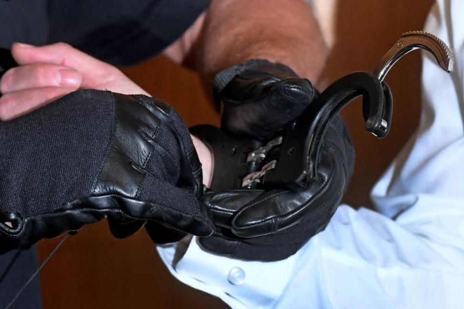 Die Handschellen werden dem Angeklagten zu Beginn eines Revisionsprozesses im Gerichtssaal im Landgericht abgenommen.
