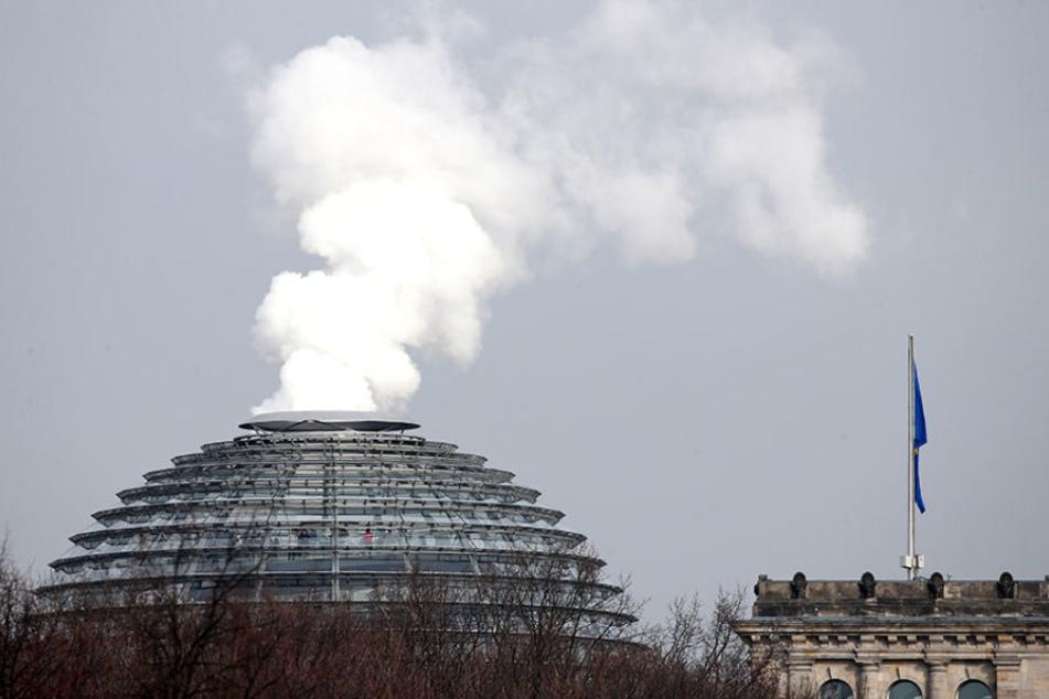 Rauch scheint aus der Kuppel des Berliner Reichstags aufzusteigen.