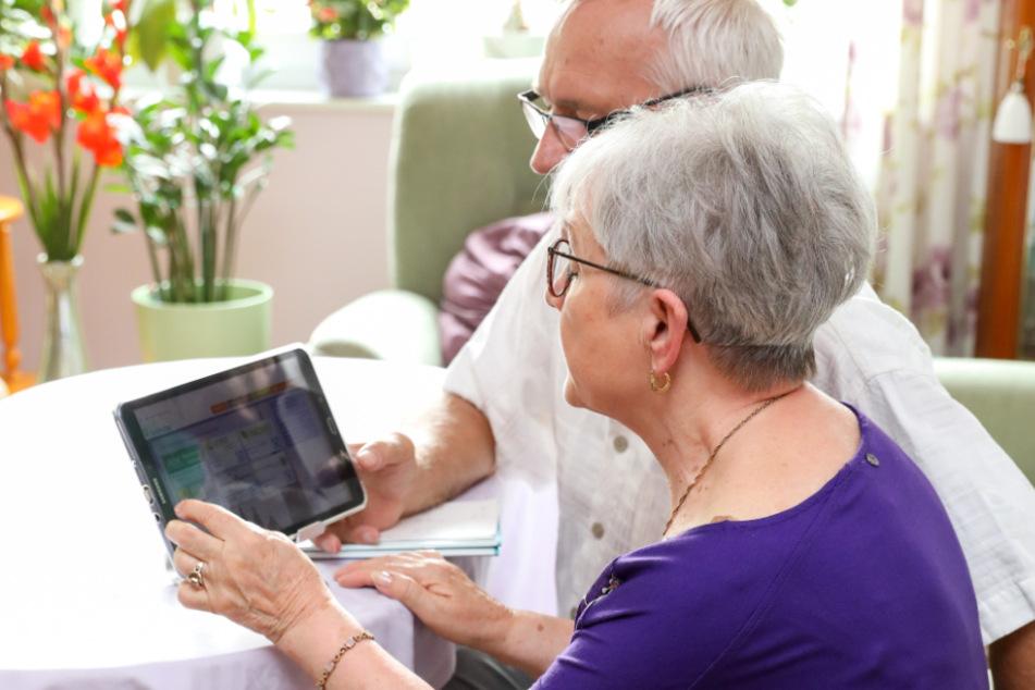 Ein Ehepaar benutzt ein Tablet für die Kommunikation mit ihrem Hausarzt. Telemedizin kann gerade für ältere Menschen eine große Hilfe sein.