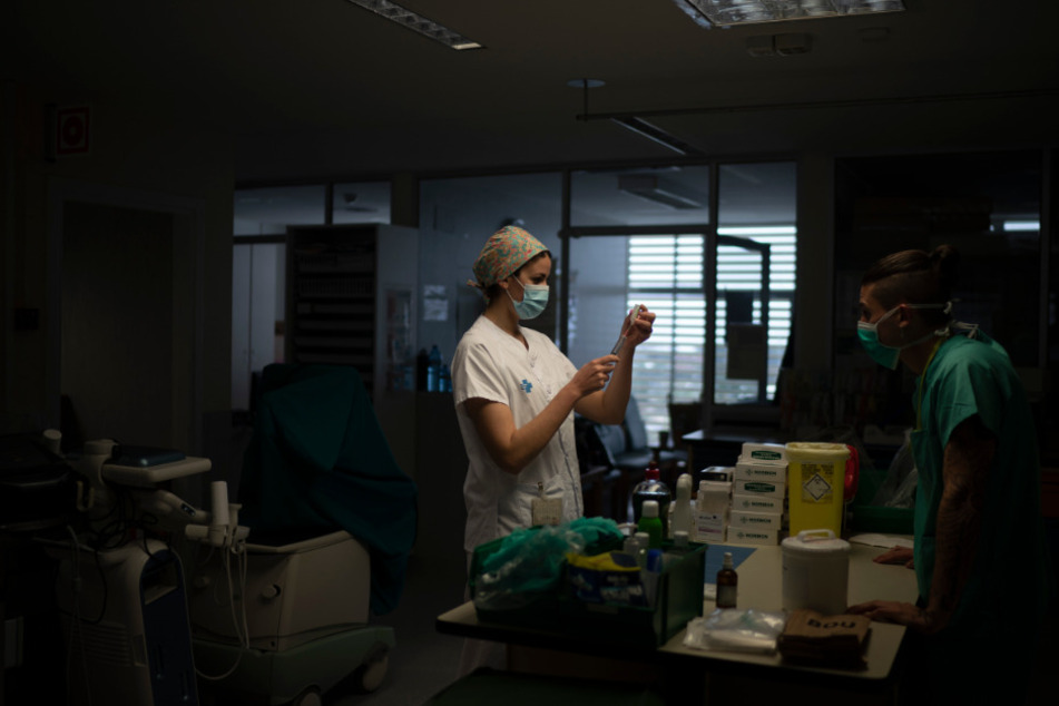 Krankenpfleger bereiten in einer Intensivstation Medikamente für einen Covid-19-Patienten vor.