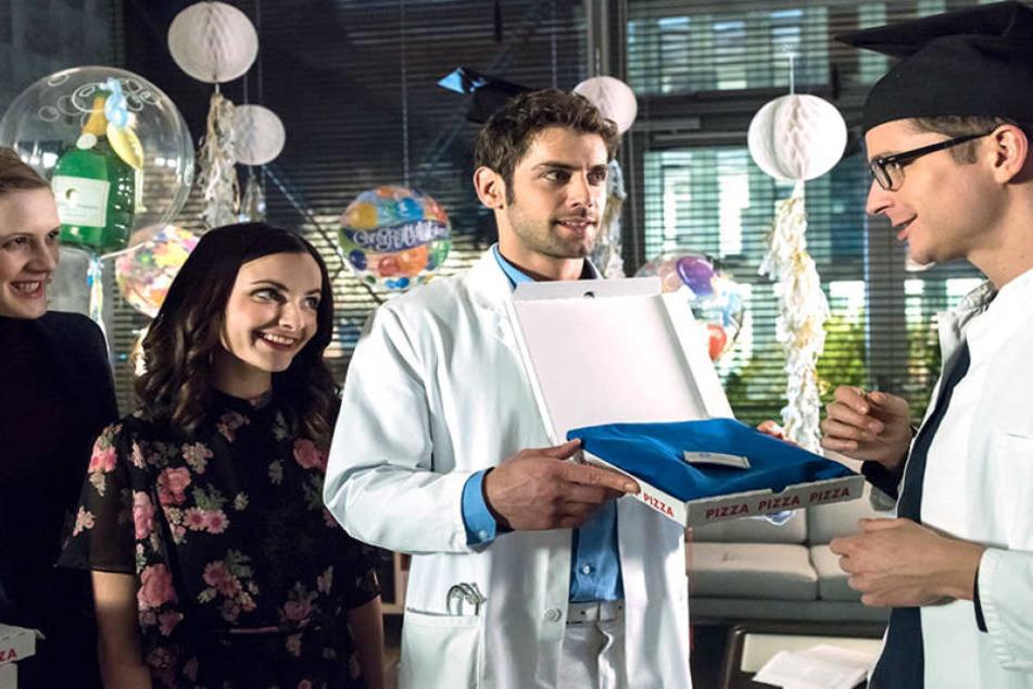 Eine Szene aus der 100. Folge. Dr. Niklas Ahrend übergibt ein neues Namensschild an den frisch examinierten Dr. Elias Bähr (Stefan Ruppe).