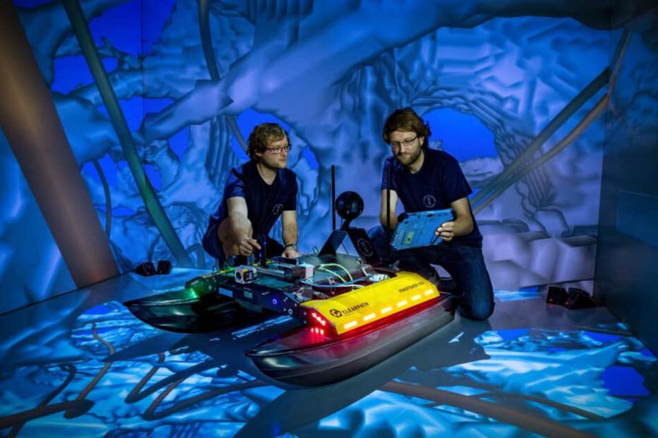 """Die TU-Informatiker Robert Lösch (r.) und Mark Sastuba zeigen den neu entwickelten Schwimmroboter """"Elisabeth"""" in einem Virtual-Reality-Raum."""