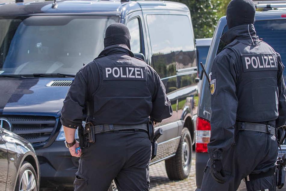 Polizisten einer Spezialeinheit gehen auf ein Grundstück in Banzkow (Mecklenburg-Vorpommern).
