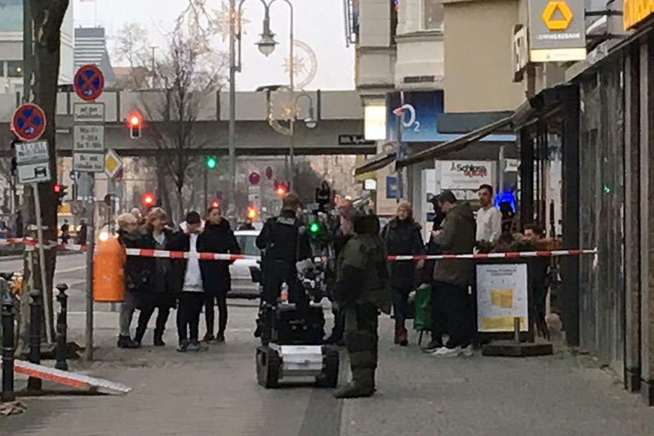 Ein Polizist und ein Sprengstoffroboter stehen vor der Bankfiliale in der Schlossstraße.
