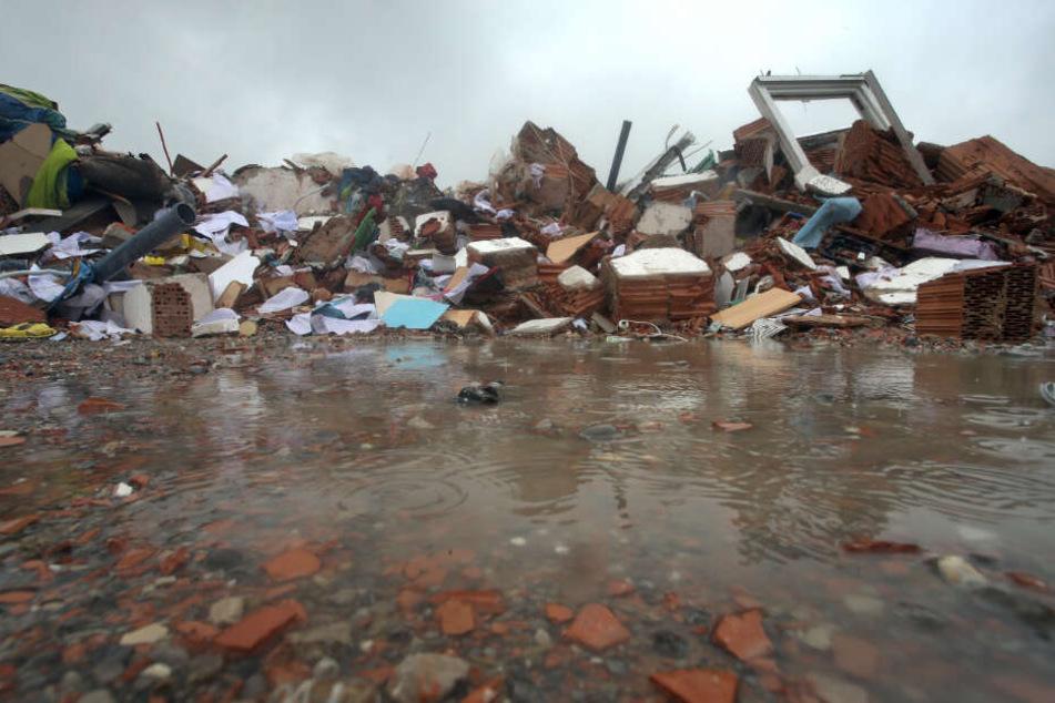 Trümmer eines explodierten Wohnhauses liegen auf einem Parkplatz nahe der Unglücksstelle im Regen.