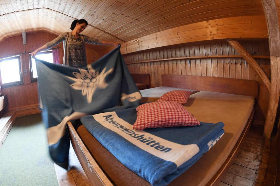 Hüttenpersonal legt die neuen hellblauen DAV Decken in einem Lager auf dem Kreuzeckhaus im Wettersteingebirge zusammen.