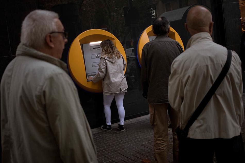 Bankkunden heben in Barcelona Bargeld von Geldautomaten ab.