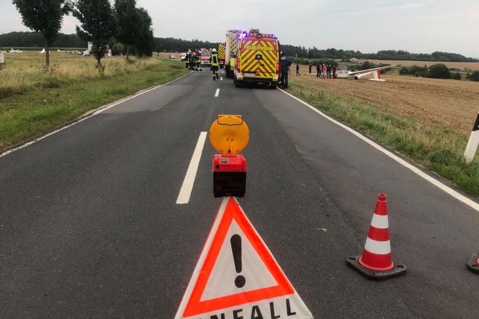 Rettungskräfte sind am Unfallort. Im Hintergrund ist der abgestürzte Flieger zu erkennen.