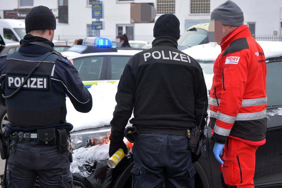 Polizei und Sanitäter stehen am Unfallfahrzeug.