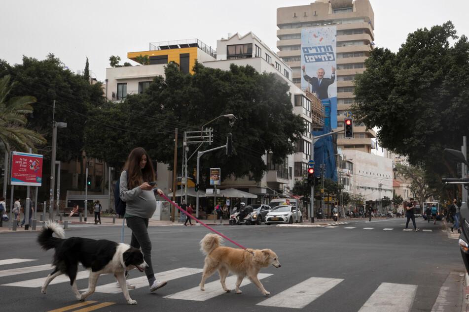 Tel Aviv: Eine Passantin geht mit Hunden an einer Gebäudewand vorbei.