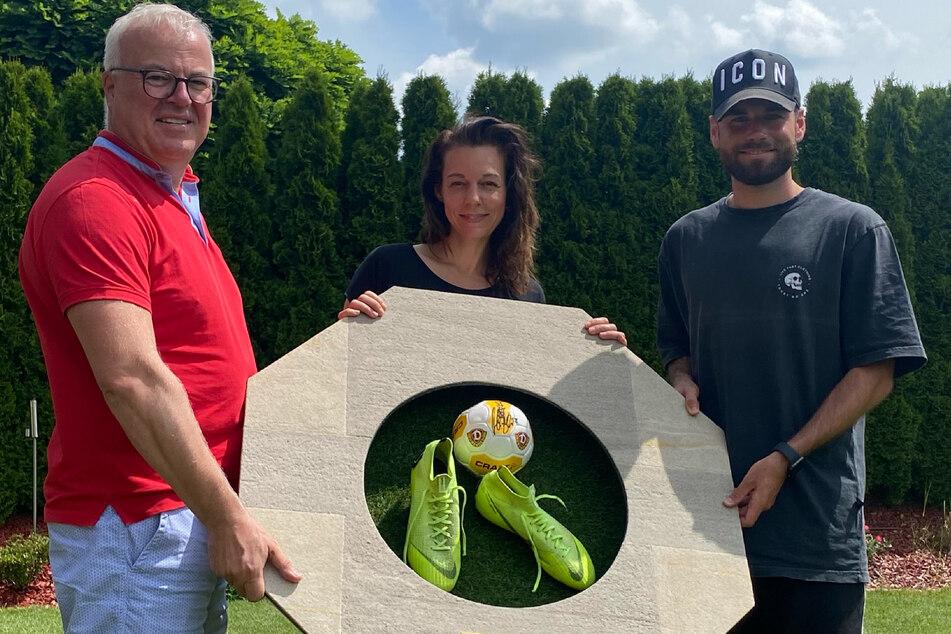 Frank Schröder (52, v.l.), Mirjam Köfer (47) und Kicker Niklas Kreuzer (28) zeigen das Wandobjekt, das bei eBay versteigert wird.