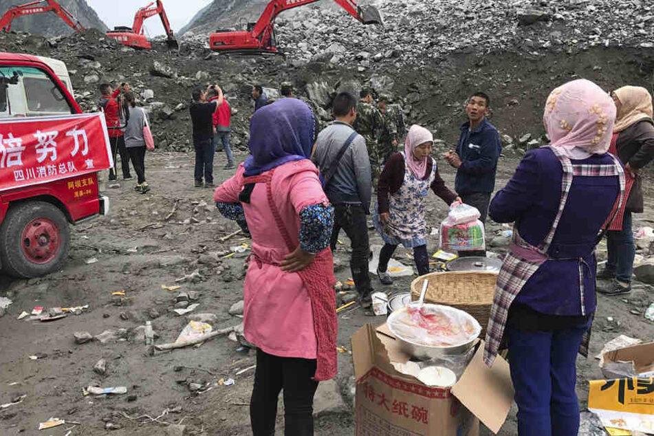 Frauen warten mit Essen, während mit Baggern in dem Geröll nach dem Bergrutsch gearbeitet wird.