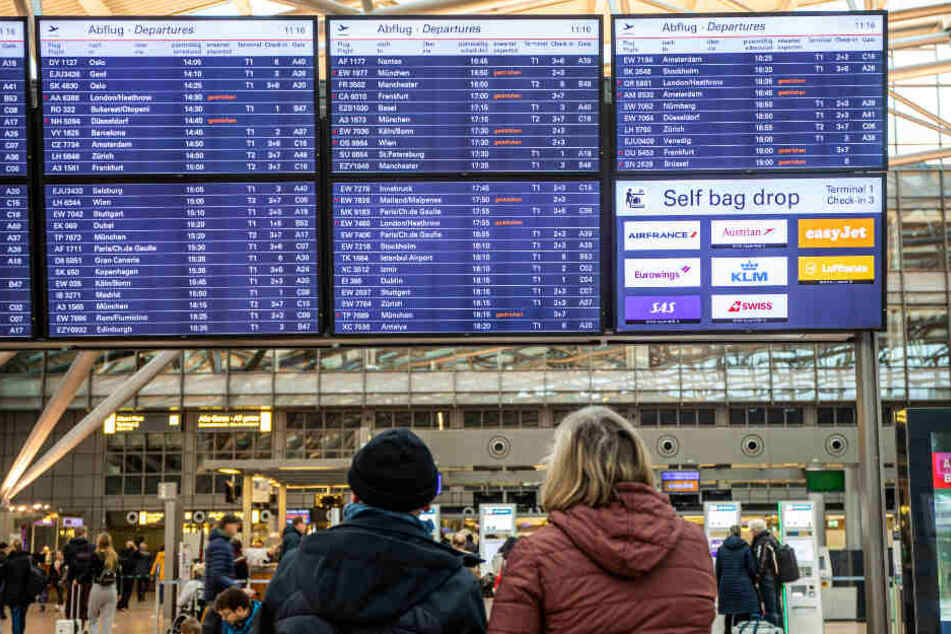 Passagiere informieren sich über die gestrichenen Flüge am Flughafen Hamburg.