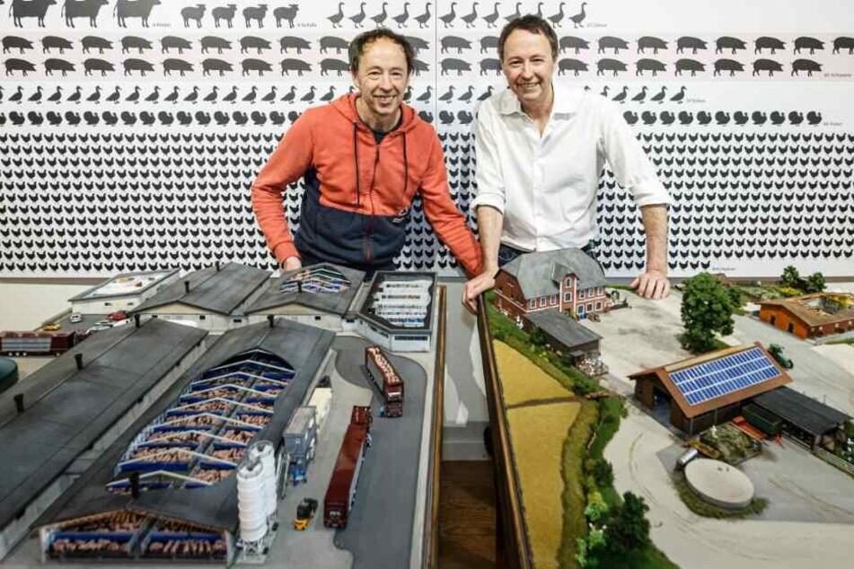 Gerrit (l) und Frederik Braun, Gründer des Miniatur Wunderlands, stehen in ihrer neuesten Ausstellung hinter einem Modell.
